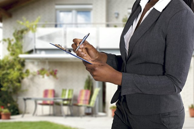 Person Filling Document In Front Of House